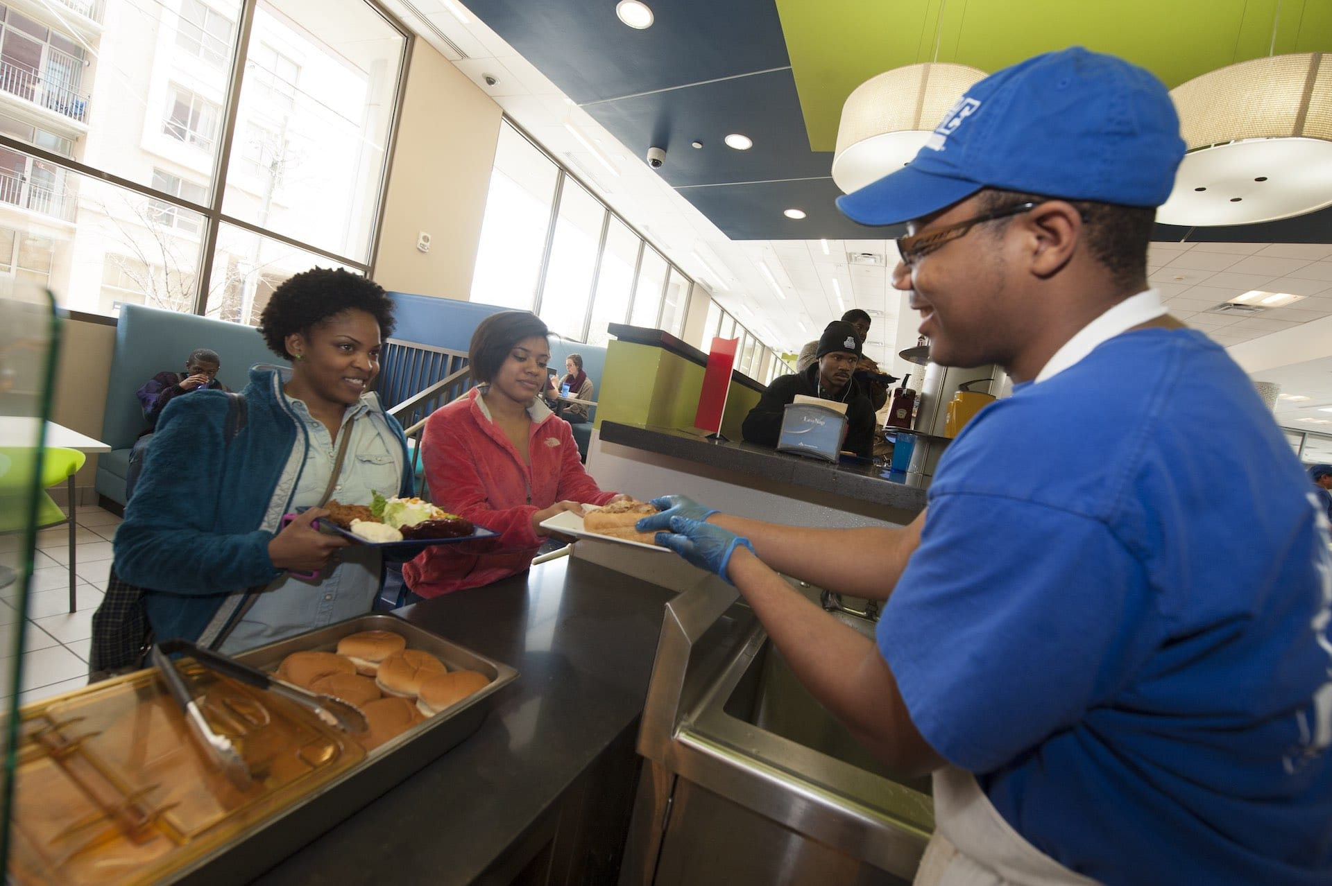 Dining hall staff serving food to students